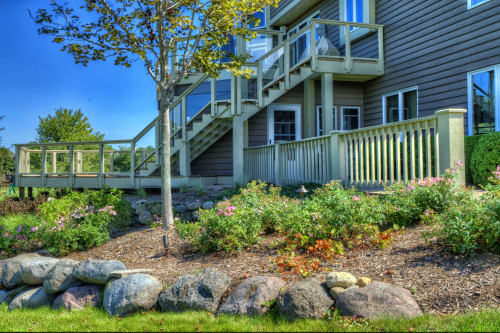 A beautiful backyard landscape with a large two story deck