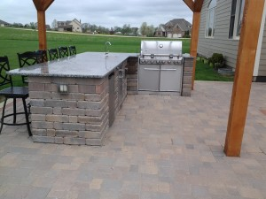Great outdoor grilling aera with a grill and a full countertop bar