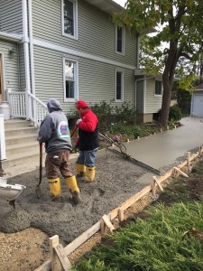 Men pouring a concrete walkway in front of a home
