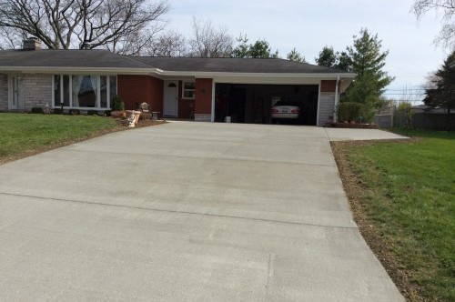 Wide concrete driveway leading up a ranch style home