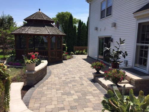 A brick paved patio in a backyard leading to a gazebo