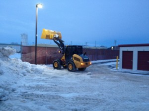 Bobcat plowing a self storage parking lot late at night