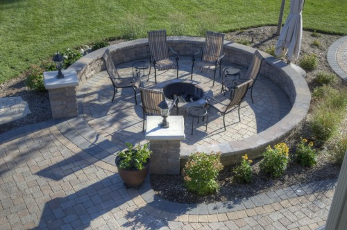 A six person fire pit located in the center of a circular brick paver patio