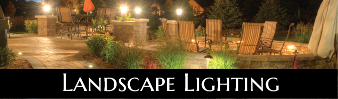 A photo taken at night featuring a well lit brick paver patio